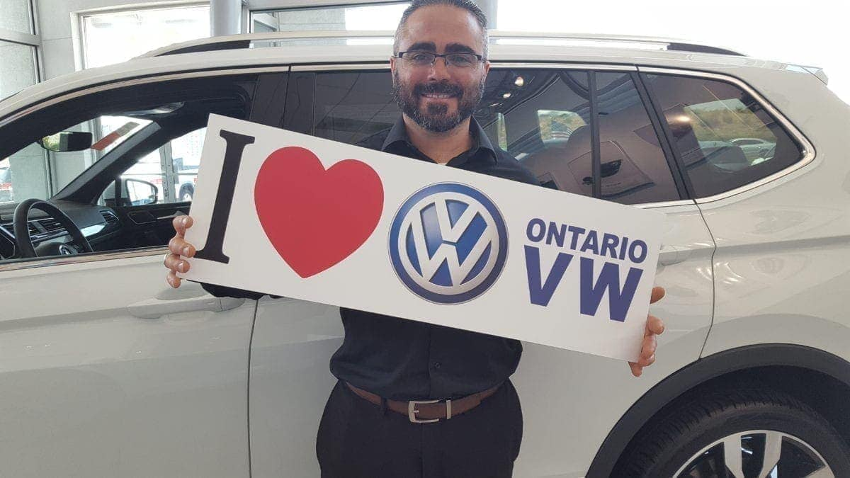 Shant Bashian standing in front of a white VW holding a sign that says